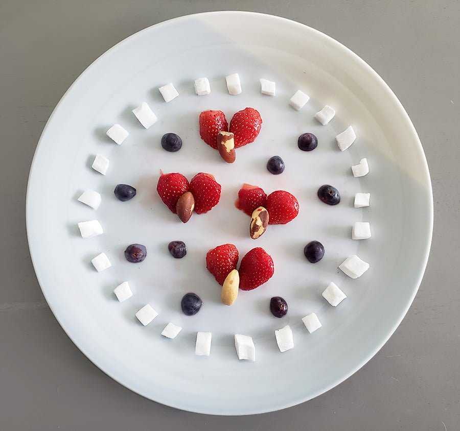 A photo of a plate with strawberries, blueberries, Brazil nuts, and pieces of coconut arranged to look something like ladybugs with decorations around them.