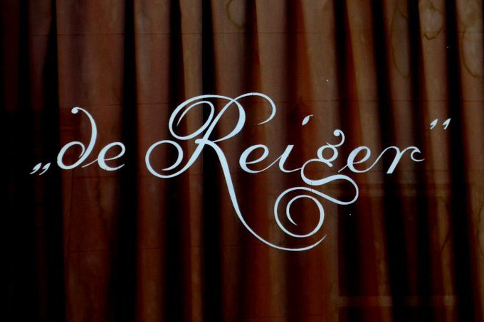 A window with the name 'de Reiger' in a beautiful curly script.