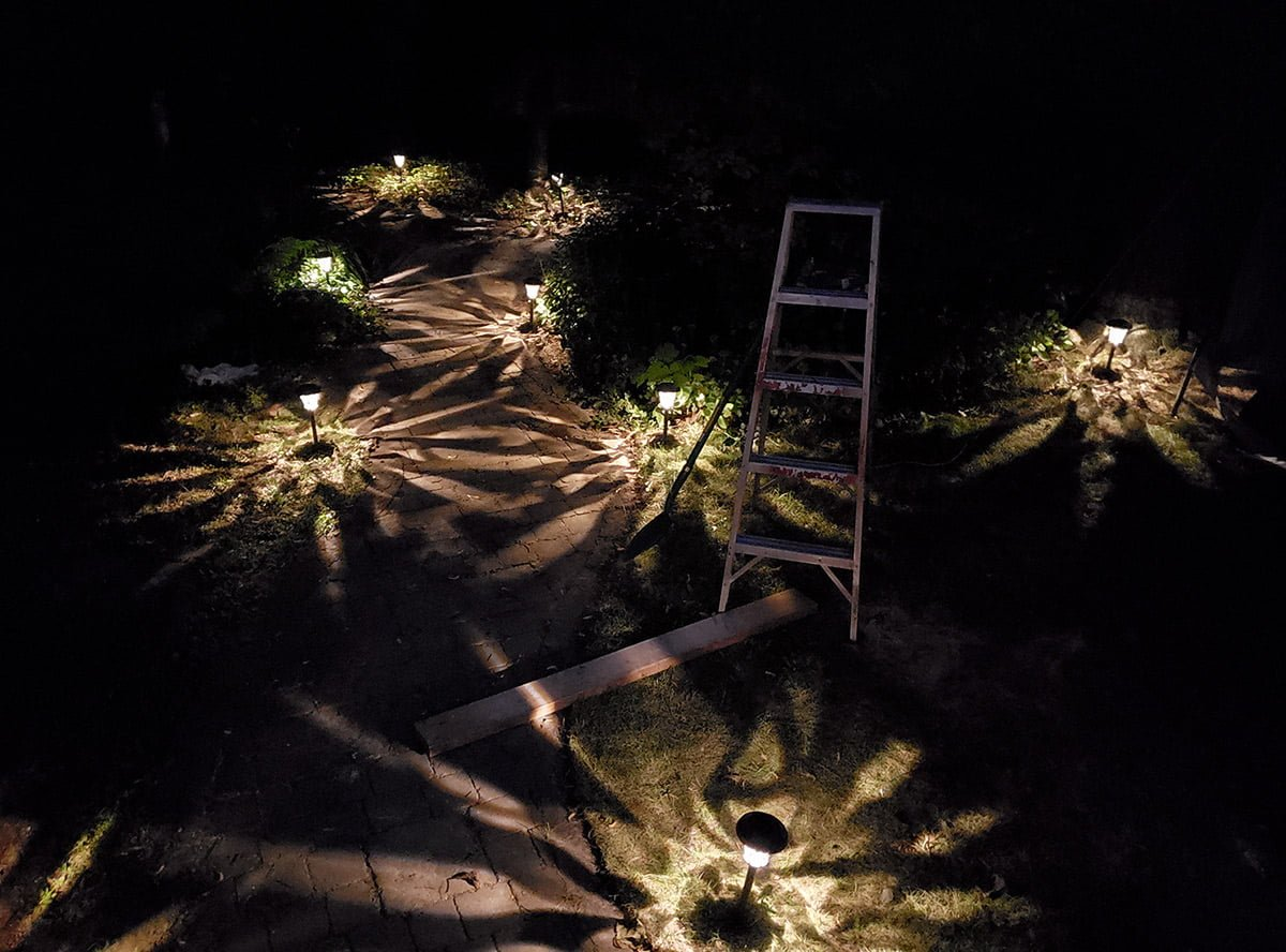 A photo of our back garden at night, showing eight lamps, a ladder, and a wooden plank.